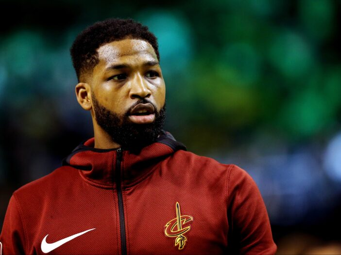 Tristan Thompson wears his red warm up sweat suit as he plays on a basketball court
