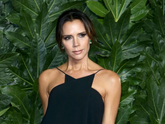 Victoria Beckham in a black dress, in front of a green plant.