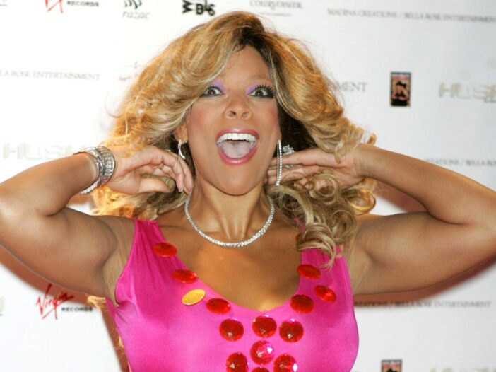 Wendy Williams pushes her hair back as she wears a pink dress against a white background
