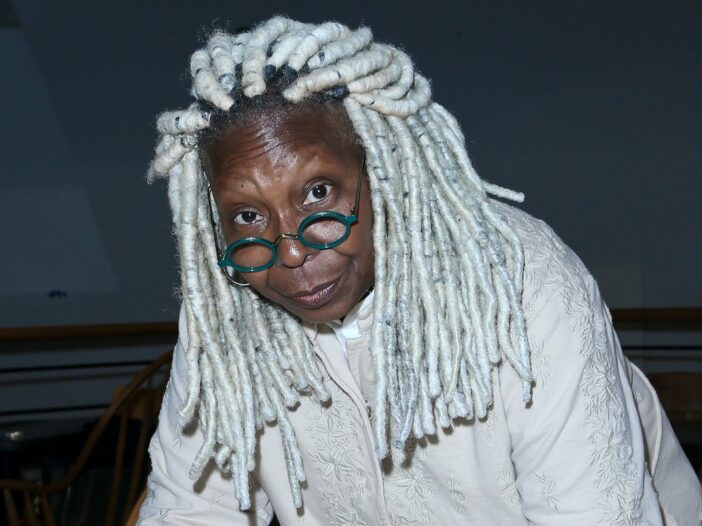 Whoopi Goldberg looks at the camera in a white top with long white locs