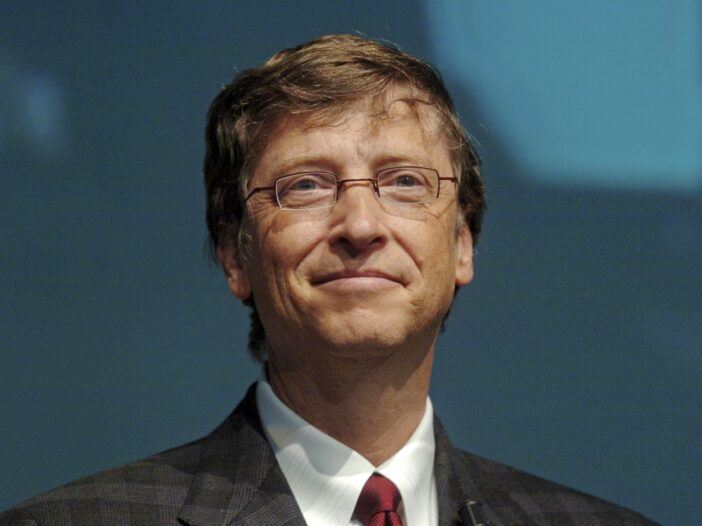 Bill Gates smiling and wearing a suit with a red tie.