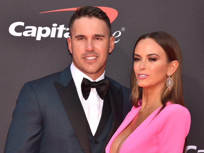 Brooks Koepka posing with his girlfriend, Jena Sims. Koepka is wearing a black suit and Sims is wearing a hot pink dress.