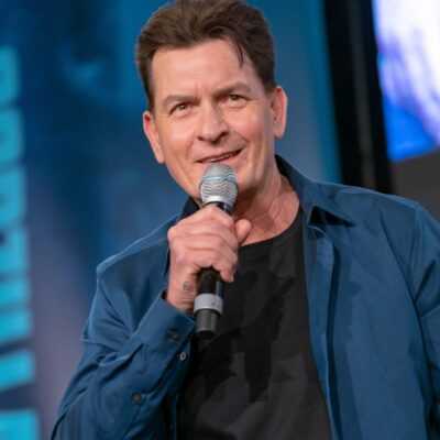 Charlie Sheen speaking into a microphone while wearing a blue jacket and a black shirt.