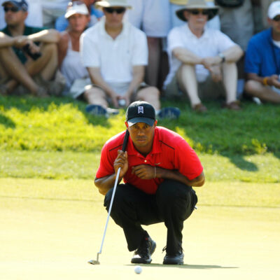 Tiger Woods crouching on a golf course