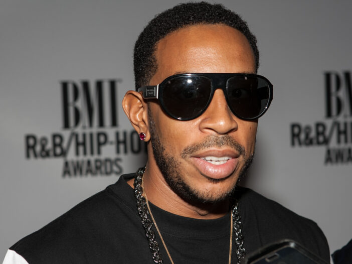 Ludacris wearing a black shirt, black sunglasses, and a black necklace.