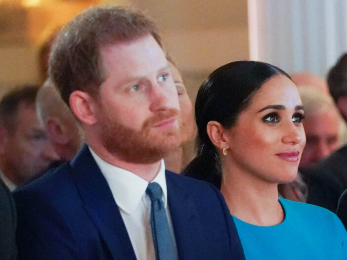 Prince harry in a blue suit with Meghan Markle in a blue dress