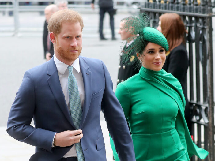 Prince Harry in a suit and Meghan Markle in a green dress