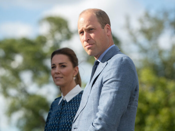 Prince William in a grey suit with Kate Middleton in the background