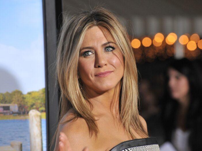 Jennifer Aniston smiling, waving, and wearing a black and white dress.