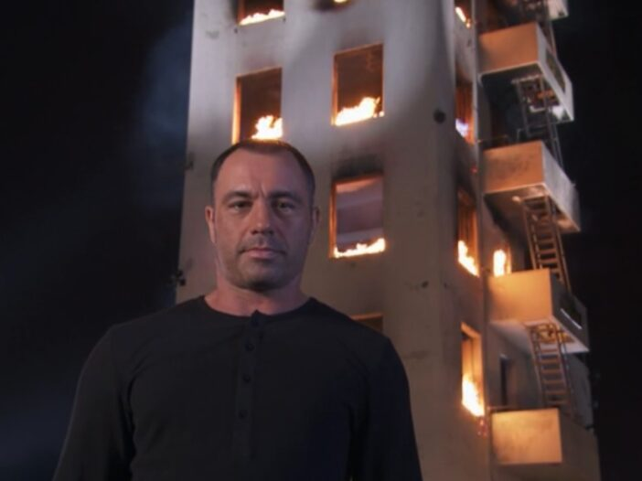 Joe Rogan standing in front of a burning building, wearing a black shirt and a blank facial expression.