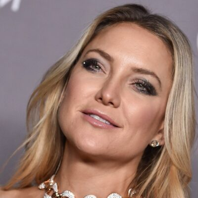 Kate Hudson wears a strapless gown and smiles in front of a gray background