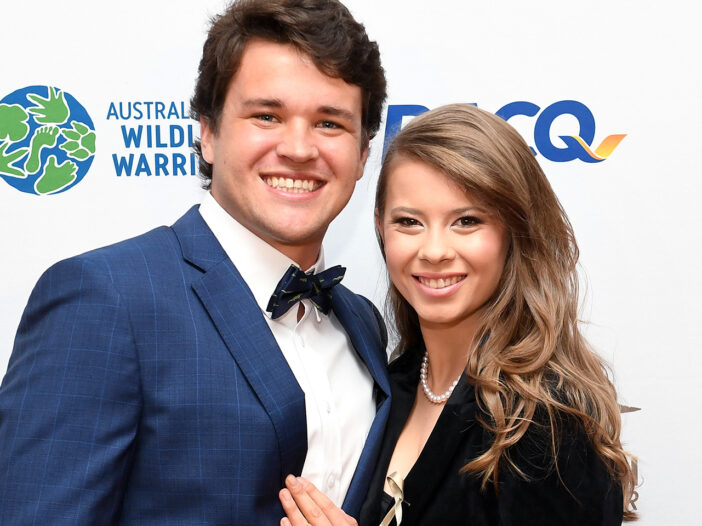 Chandler Powell in a blue suit, standing with Bindi Irwin in a black outfit.