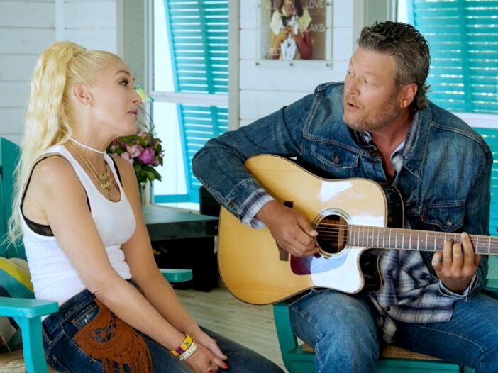 Gwen Stefani and Blake Shelton sitting together, singing, with Shelton playing guitar.