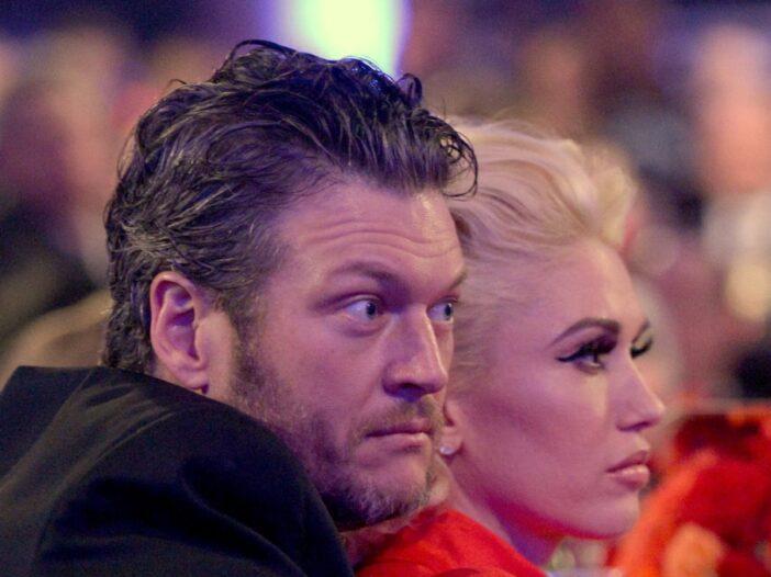 Blake Shelton, in a dark blazer, cuddles up with Gwen Stefani, in a red dress