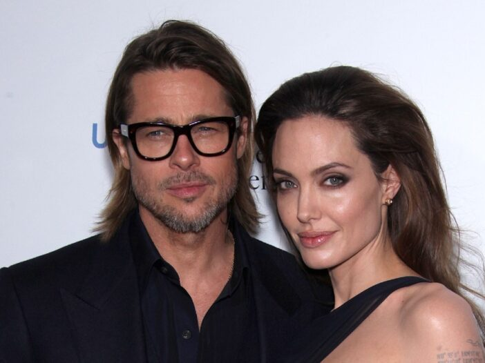 Brad Pitt and Angelina Jolie, both dressed in black, pose in front of a white background
