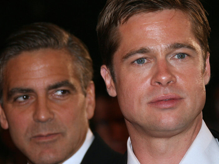 Close up of Brad Pitt with George Clooney side-eying him from behind.