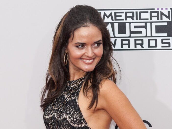 Danica McKellar looks over her shoulder as she wears a black dress to the AMAs