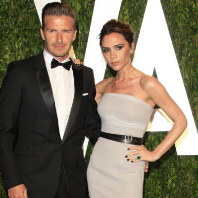 David Beckham on the right in a tuxedo, Victoria Beckham on the right in a gray halter top dress.