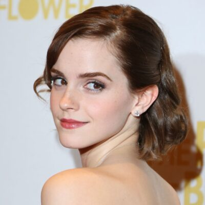 Emma Watson looks over her shoulder while wearing a strapless gown