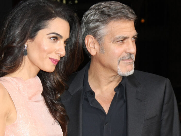 Amal Clooney on the left in a pink dress, George Clooney on the right in a dark suit