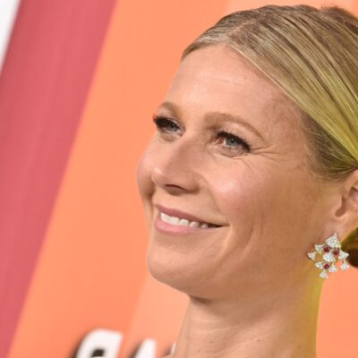 Gwyneth Paltrow stands before a colorful background and smiles at the cameras