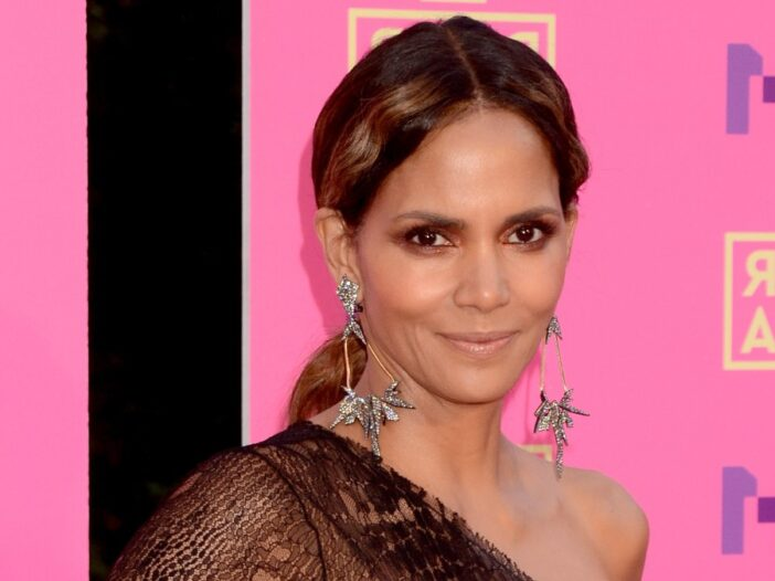 Halle Berry wears a rust colored, off the shoulder dress against a pink background
