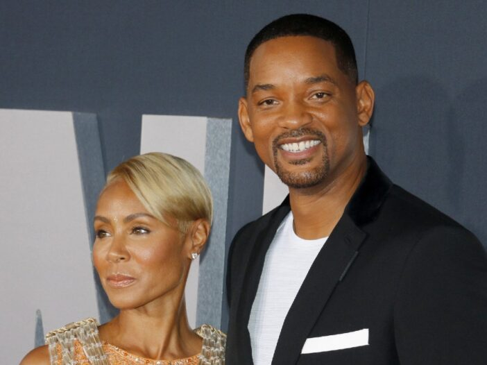 Jada Pinkett Smith looks to the right as Will Smith looks forward with a smile