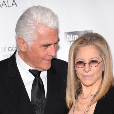 James Brolin looks down at Barbra Streisand in front of a white background