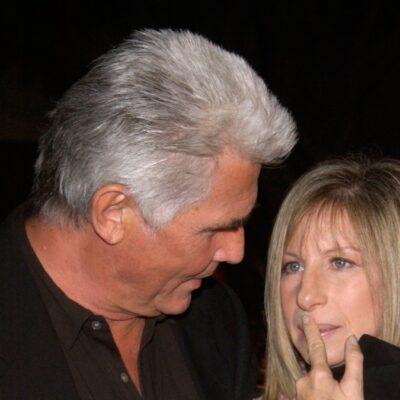 James Brolin leans down to look at Barbra Streisand, who holds a finger to her lips