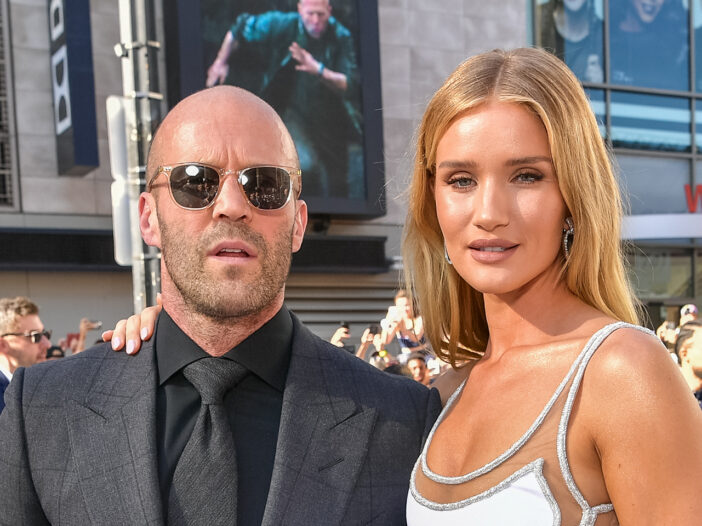 Jason Statham on the left in sunglasses and a suit, Rosie Huntington-Whiteley on the right in a white dress