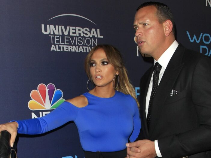 Jennifer Lopez, in a blue dress, points to something as Alex Rodriguez, black suit, looks on