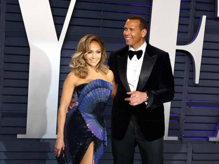 Jennifer Lopez in a dramic blue dress, standing next to Alex Rodriguez in a tux, looking to the right