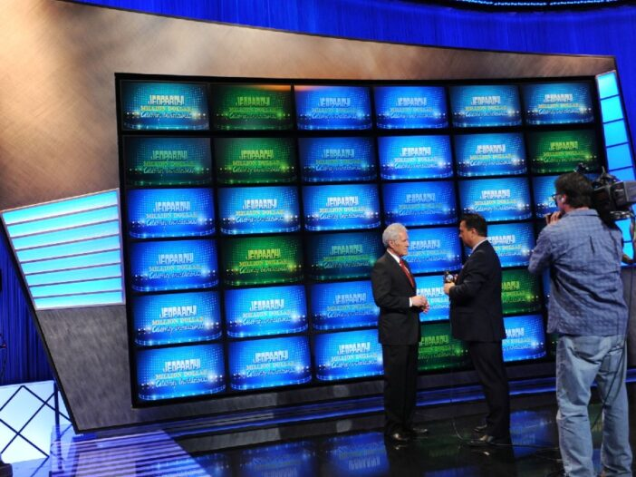 Alex Trebek speaks with another man on the set of Jeopardy