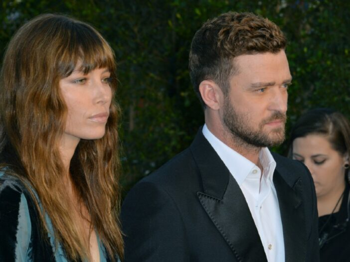 Jessica Biel, in a multicolored dress, walks with Justin Timberlake, in a black suit, on the red carpet