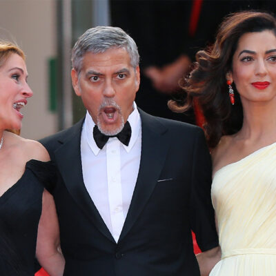 George Clooney making a funny face while standing with a laughing Julia Roberts on his right and Amal Clooney looking away on his left.