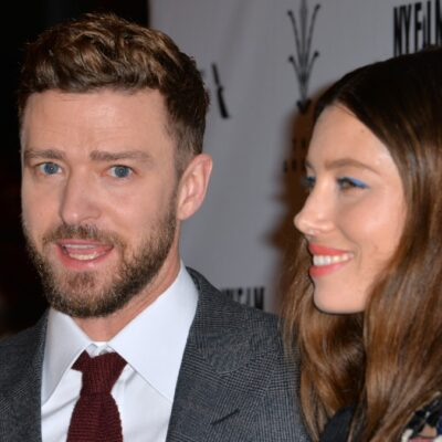 Justin Timberlake, in a gray suit, stands with Jessica Biel, in a patterned dress