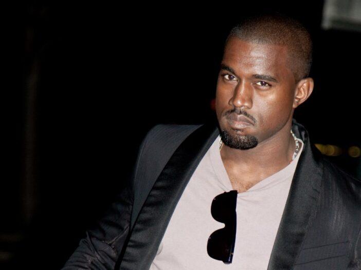 Kanye West wears a black blazer over a beige t shirt