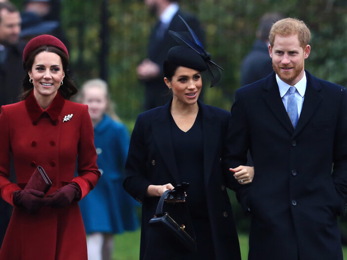 From left to right, Kate Middleton, Meghan Markle, Prince Harry, walking together.