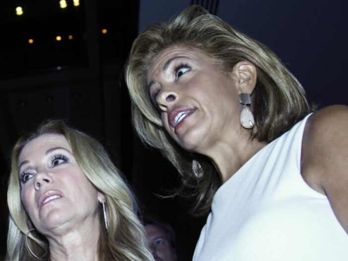 Kathie Lee Gifford and Hoda Kotb, in a white dress, stand close together as they're photographed from below