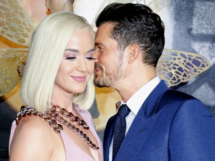 Katy Perry wearing a pink dress stands with Orlando Bloom, in a blue suit