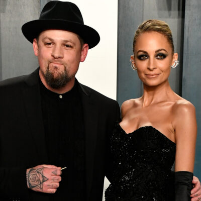 Joel Madden in all black wearing a hat, standing with Nicole Richie in a black dress