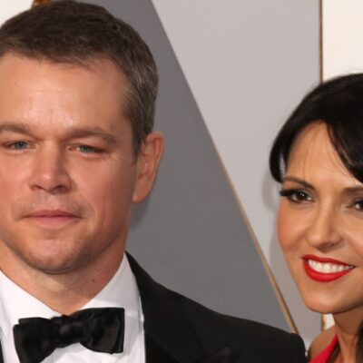 Matt Damon wearing a black tux stands with his wife, Luciana Barraso, in a red dress