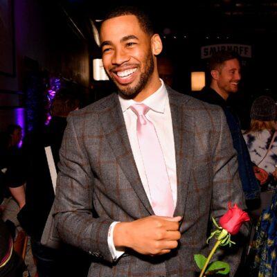Matt James wears a dark suit as he holds a red rose