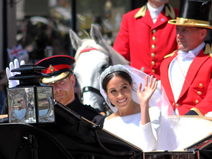 Prince Harry and Meghan Markle ride in an open carriage on the day of their wedding
