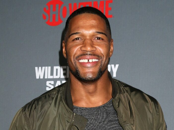 Michael Strahan wears a green jacket over a dark t shirt on the red carpet