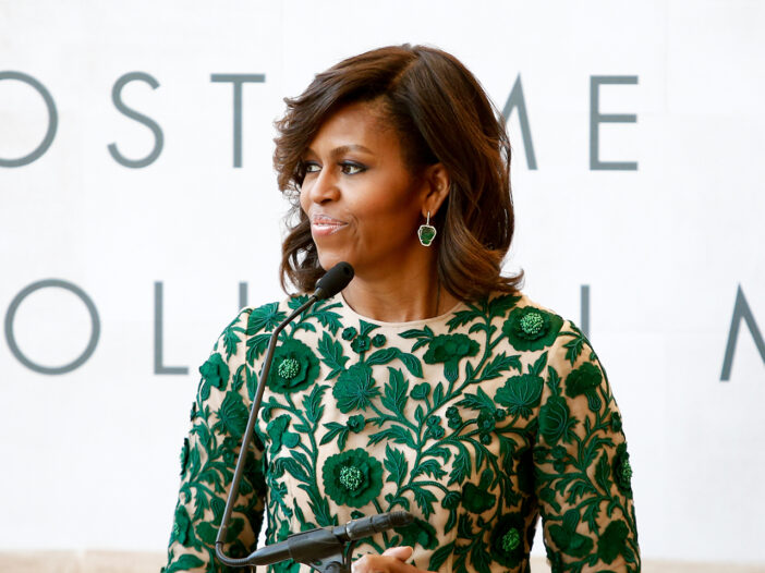 Michelle Obama looking to the rightm where a green and yellow dress.