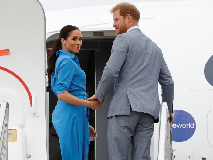Meghan Markle and Prince Harry walking on a plane and looking back to the cameras