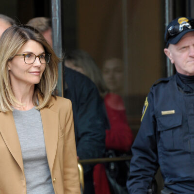 Lori Loughlin leaving a courthouse with a police officer to her left.