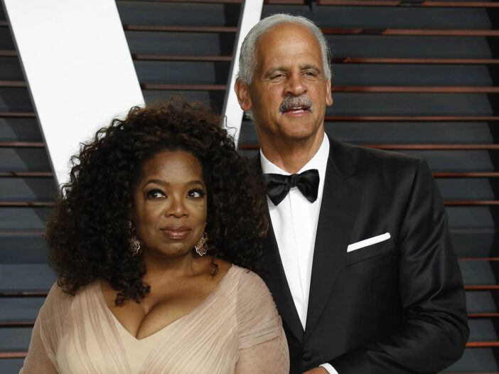 Oprah Winfrey on the left, looking surprised and standing with Stedman Graham, on the right