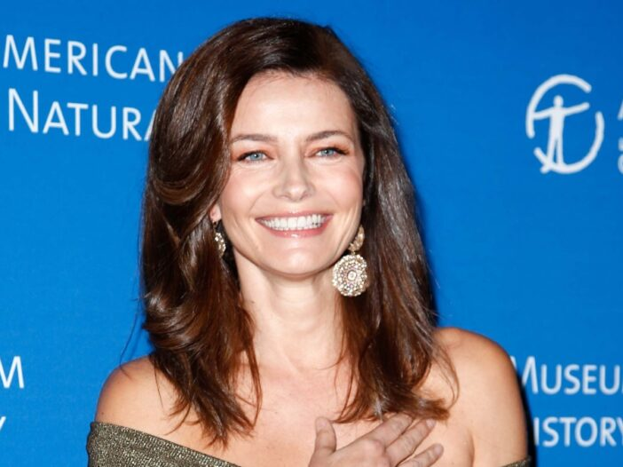 Paulina Porizkova wears an off the shoulder green dress in front of a blue background